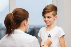 Doctor with stethoscope listening to happy child Stock Images