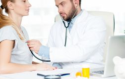 Doctor with stethoscope listening to the patient. Doctor checking heart beat of patient Royalty Free Stock Image