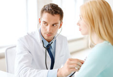 Doctor with stethoscope listening to the patient stock images