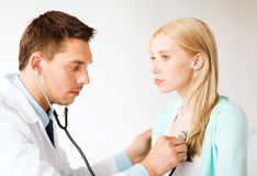 Doctor with stethoscope listening to the patient Royalty Free Stock Photography
