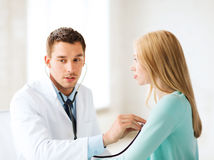 Doctor with stethoscope listening to the patient Stock Photos
