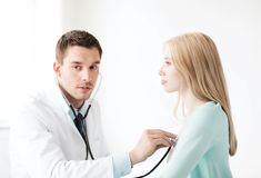Doctor with stethoscope listening to the patient Royalty Free Stock Photos