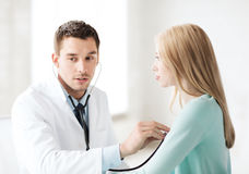 Doctor with stethoscope listening to the patient Stock Photo