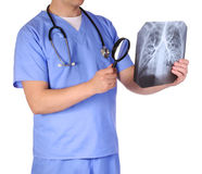 Doctor with stethoscope and magnifying glass examining x-ray Stock Image