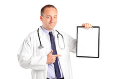 Doctor with stethoscope pointing on a clipboard Royalty Free Stock Images