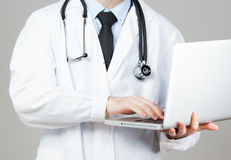 Doctor with stethoscope. Serious doctor with stethoscope and laptop Stock Photography