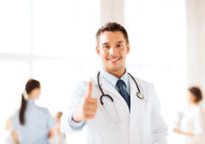 Doctor with stethoscope showing thumbs up. Healthcare and medical concept - doctor with stethoscope showing thumbs up Royalty Free Stock Images
