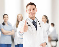 Doctor with stethoscope showing thumbs up. Healthcare and medical concept - doctor with stethoscope showing thumbs up Royalty Free Stock Photography