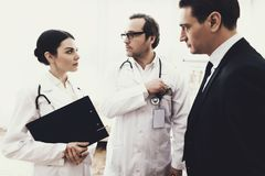Doctor with stethoscope takes bribe from successful businessman, looking around. Bribe. royalty free stock image