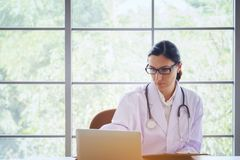 Doctor with Stethoscope working writing on paperwork with clipboard and laptop computer on table in the hospital. Doctor Writing. On A Document In He`s Practice royalty free stock images