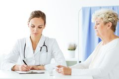 Doctor with stethoscope writing prescription. General doctor with stethoscope writing a prescription for a women with a cold Royalty Free Stock Photography