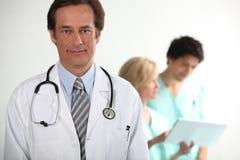 Doctor stod med kollegor Royaltyfri Foto