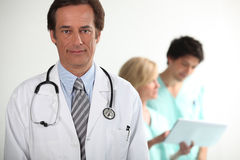 Doctor stood with colleagues Royalty Free Stock Photo