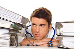 Doctor on stress with stacks of files. Bureaucracy