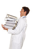 Doctor on stress with stacks of files. Bureaucracy Royalty Free Stock Photo