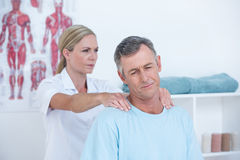 Doctor stretching her patient neck Royalty Free Stock Photography