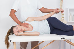 Doctor stretching his patient arm Stock Photo