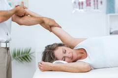 Doctor stretching his patients arm Royalty Free Stock Photo