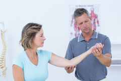 Doctor stretching his patients arm royalty free stock images