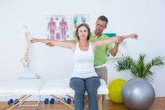 Doctor stretching his patients arms Stock Image