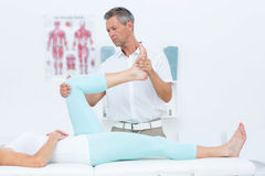 Doctor stretching his patients leg Royalty Free Stock Images