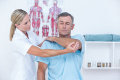 Doctor stretching a man arm Royalty Free Stock Photo