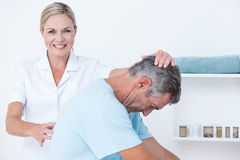 Doctor stretching a man back royalty free stock image