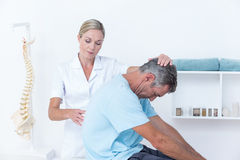Doctor stretching a man back royalty free stock photography