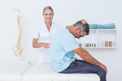 Doctor stretching a man back Royalty Free Stock Photo