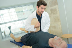 Doctor stretching mans leg on physiotherapy session Royalty Free Stock Photography