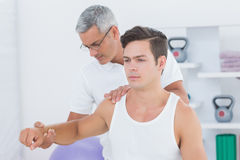Doctor stretching a young man arm Royalty Free Stock Images