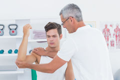 Doctor stretching a young man arm Stock Image