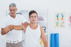 Doctor stretching a young man arm Stock Photos