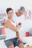 Doctor stretching a young man arm Stock Photo