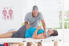 Doctor stretching a young man back Stock Images