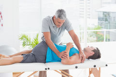 Doctor stretching a young man back Royalty Free Stock Images