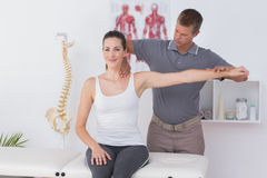 Doctor stretching a young woman arm Stock Photography
