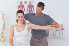 Doctor stretching a young woman arm Royalty Free Stock Photo