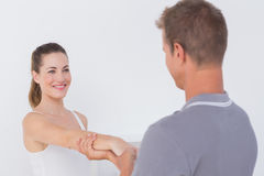 Doctor stretching a young woman arm Stock Images