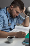 Doctor studying book. Doctor sitting at the desk and studying book Royalty Free Stock Photography