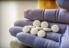 Doctor Supports In Its Hand Some White Pills. Conceptual image royalty free stock photo