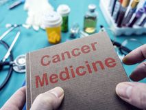 Doctor supports in its hands a book on the cancer Stock Photo