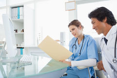 Doctor and surgeon comparing notes Royalty Free Stock Photography