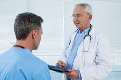 Doctor and surgeon discussing over clipboard stock photo