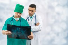 Surgeon and doctor looking at x-ray film. Doctor and surgeon examining xray film, diagnose patient `s waist bone injury. Surgery operation and medical concept Stock Photos