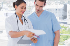 Doctor and surgeon going over notes on clipboard. By big bright windows Stock Image