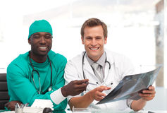 Doctor and surgeon looking at an xray and smiling Royalty Free Stock Photo