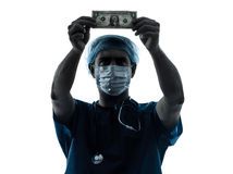 Doctor surgeon man examing dollar bill silhouette Stock Photography