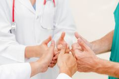 Doctor, surgeon and nurse join hands together. Medical service teamwork - Doctor, surgeon and nurse join hands together stock photography