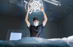 Doctor surgeon in the operating room  with lamp Stock Photography
